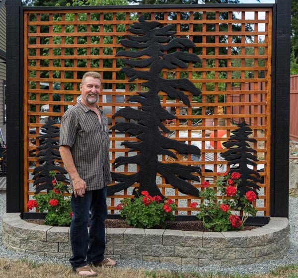 Kim Reavley, Vancouver Island wood carver, in front of a custom privacy screen
