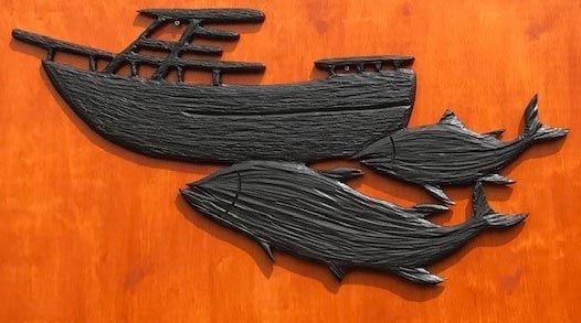 wood carving of a boat and salmon by Vancouver Island wood carver West Coast Wood Creations